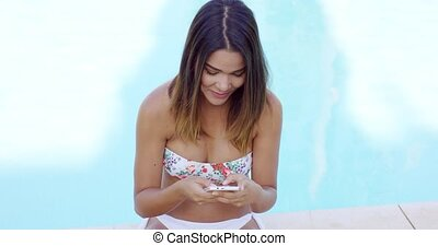 Smiling young woman reading a text message