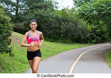 Smiling young woman running for fitness