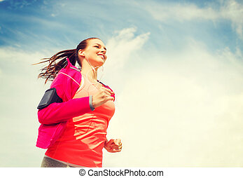 smiling young woman running outdoors - fitness, sport and ...