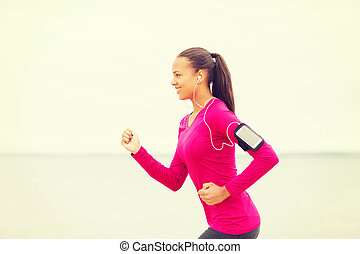 smiling young woman running outdoors - sport, fitness, ...