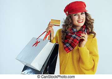 smiling young woman shopper showing golden credit card