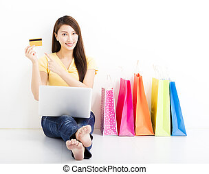 Smiling  young woman shopping with credit card