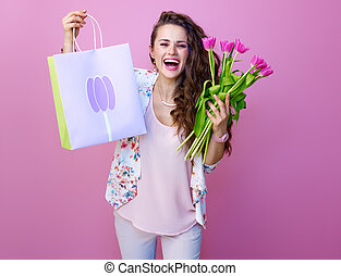 smiling young woman showing bouquet of flowers and shopping bag