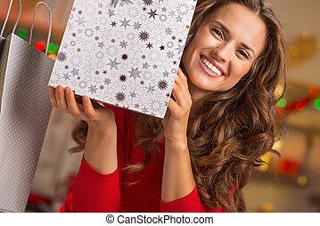 Smiling young woman showing christmas shopping bag