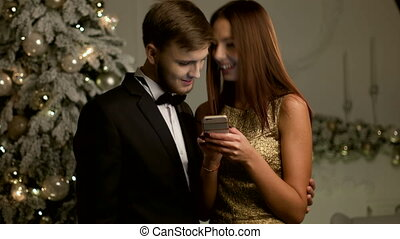 Smiling young woman showing Christmas wishes for her handsome boyfriend on smartphone.
