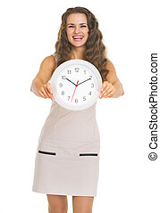 Smiling young woman showing clock