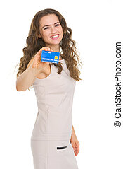 Smiling young woman showing credit card