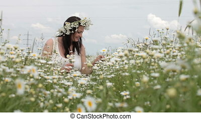 smiling young woman sitting among the daisies in the spring lawn