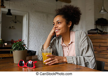 Smiling young woman sitting at home with glass of orange juice