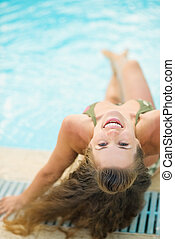 Smiling young woman sitting at poolside