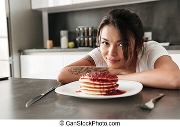 Smiling young woman sitting at the kitchen