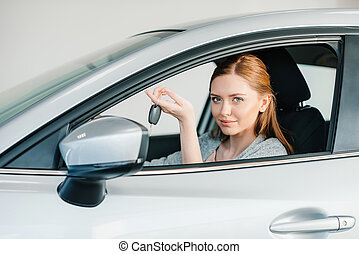 Smiling young woman sitting in new car and holding key