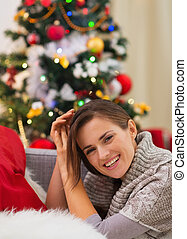 Smiling young woman sitting near Christmas tree