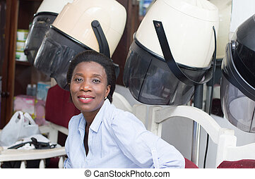 Smiling young woman sitting next to hair helmets.
