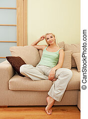 Smiling young woman sitting on a sofa