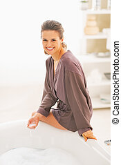 Smiling young woman sitting on bathtub