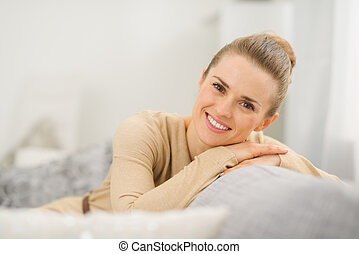 Smiling young woman sitting on couch in living room