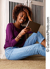 Smiling young woman sitting on floor looking at digital tablet