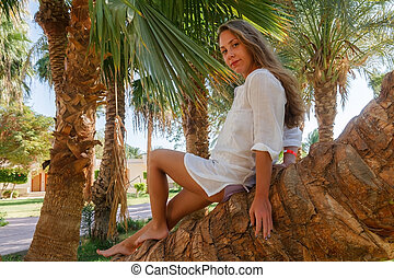 Smiling young woman sitting on palm tree. Concept happy rest, life without problems