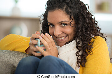 smiling young woman sitting on sofa holding cup of tea