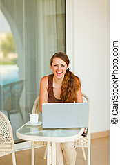 Smiling young woman sitting on terrace with cup of coffee and laptop