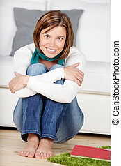 Smiling young woman sitting on the floor