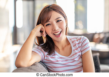 smiling young woman sitting on the sofa