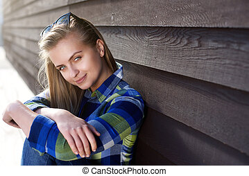 Smiling young woman sitting outside