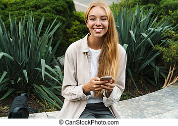 Smiling young woman sitting with cellphone