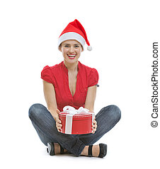 Smiling young woman sitting with Christmas present box