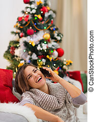 Smiling young woman speaking mobile near Christmas tree