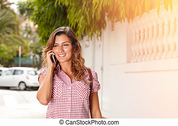 Smiling young woman speaking on cell phone