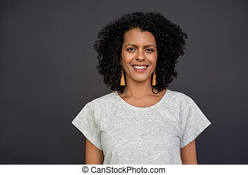 Smiling young woman standing against a gray background