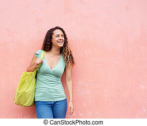 Smiling young woman standing against a wall with bag