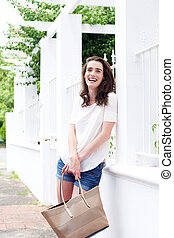 Smiling young woman standing against wall with bag