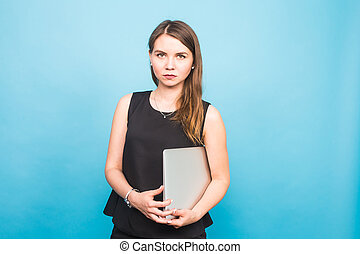 Smiling young woman standing and holding laptop over blue background
