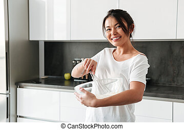 Smiling young woman standing at the kitchen in home