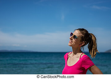 Smiling young woman standing by the sea