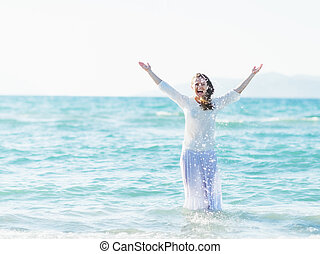 Smiling young woman standing in sea and sprinkling water