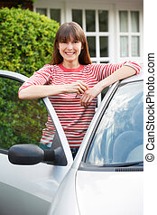 Smiling Young Woman Standing Next To Car