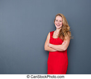 Smiling young woman standing on gray background