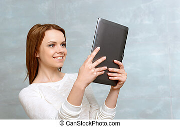 Smiling young woman standing with tablet