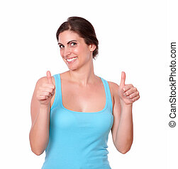 Smiling young woman standing with thumbs up