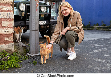 Smiling young woman stroking a stray Istanbul cat.