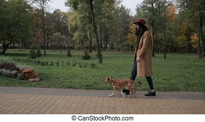Smiling young woman stroking dog in autumn park