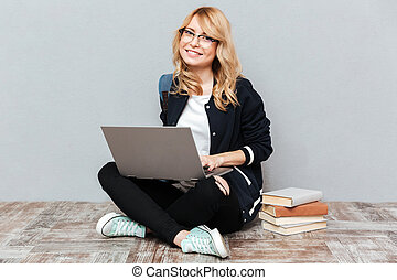 Smiling young woman student using laptop computer.