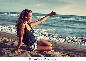selfie - smiling young woman take a selfie photo at sandy...