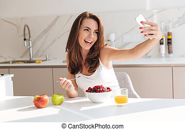 Smiling young woman taking a selfie while having healthy...
