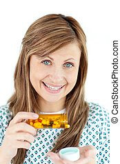 Smiling young woman taking pills