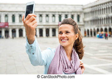 Smiling young woman taking self photo with cell phone on piazza
